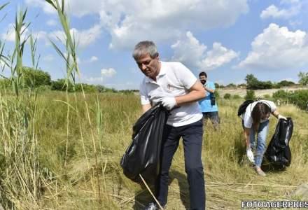 Premierul Ciolos si ministrul Mediului, voluntari la strans gunoaie in Delta Vacaresti